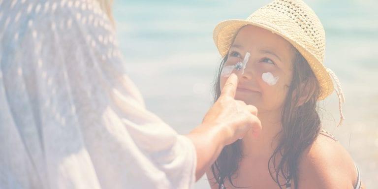 Mom putting sunscreen on girl