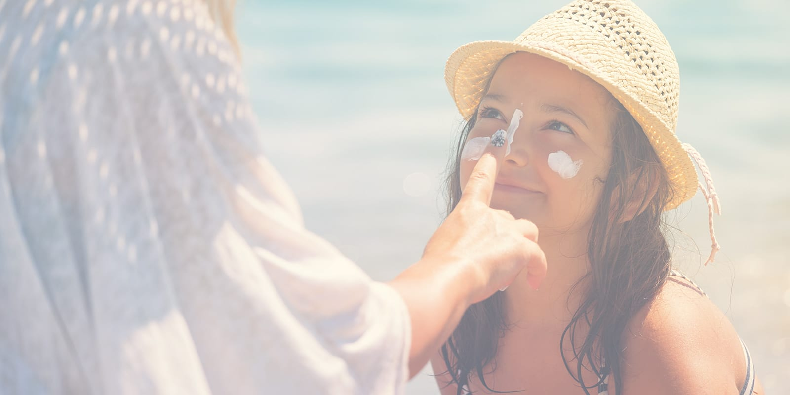 A mom putting sun screen on her daughter's face