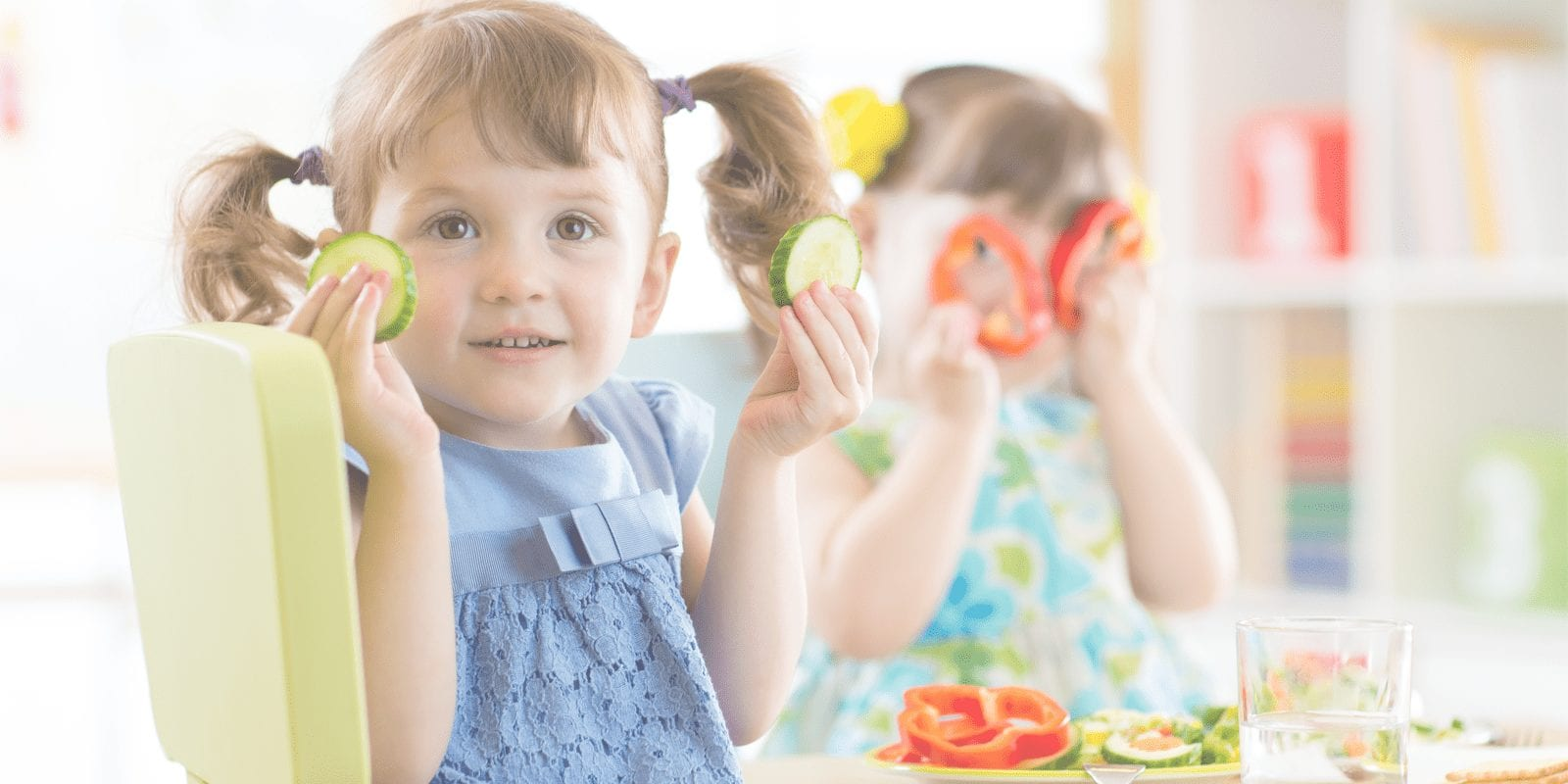 Two little girls playing and eating with vegetables