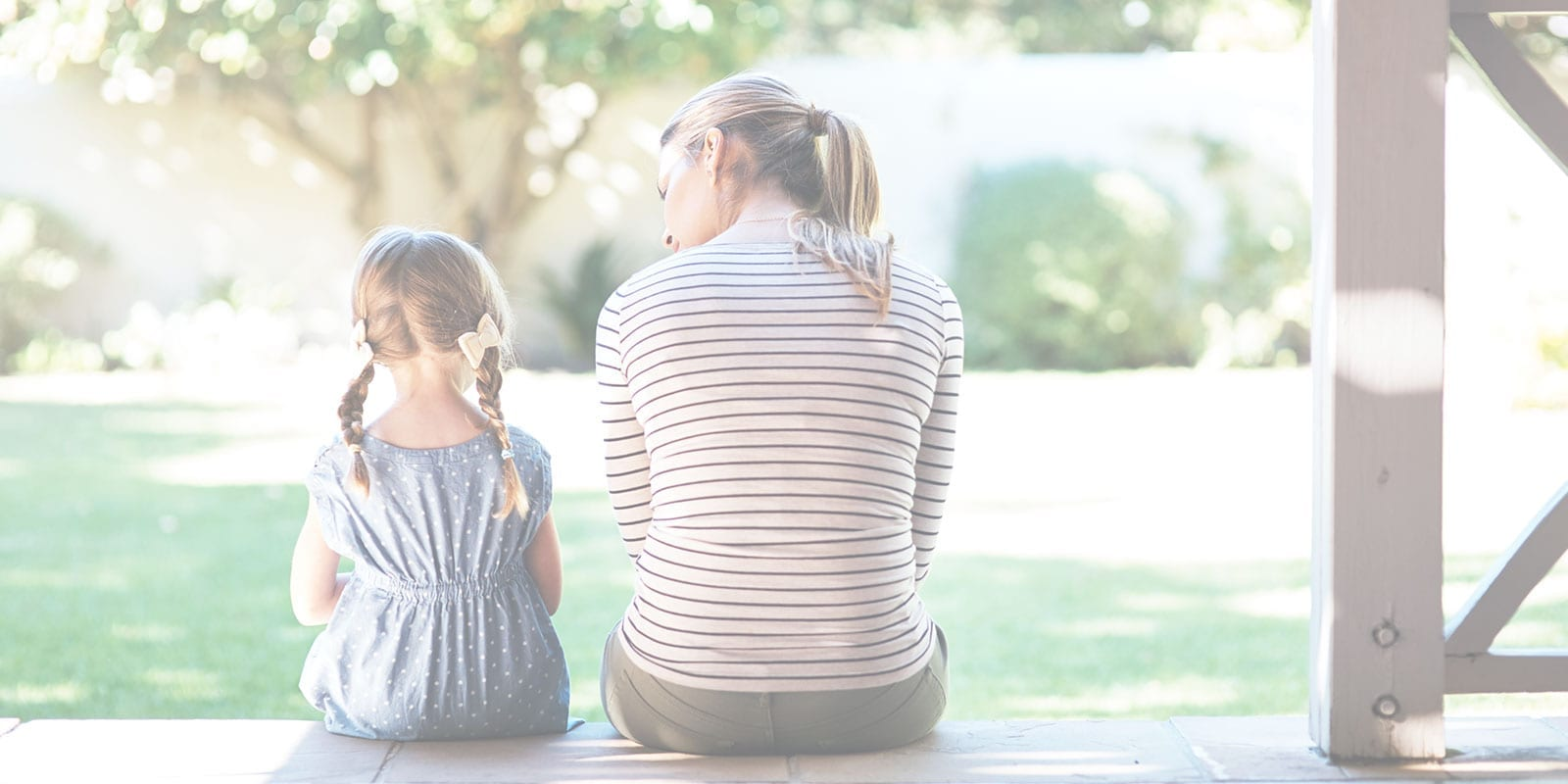 A mom and daughter sitting on porch together having a conversation