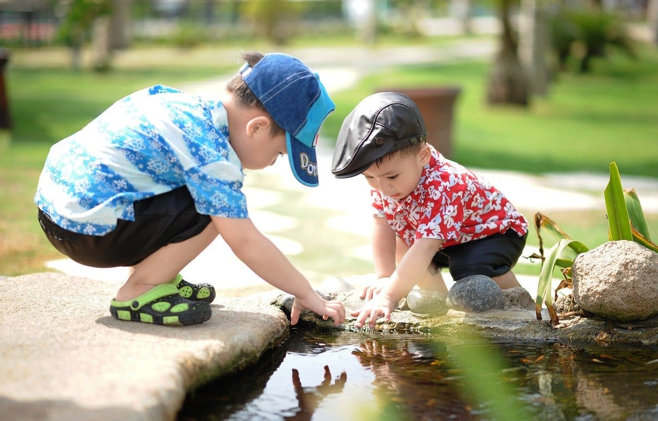 Children playing with rocks and water in a park