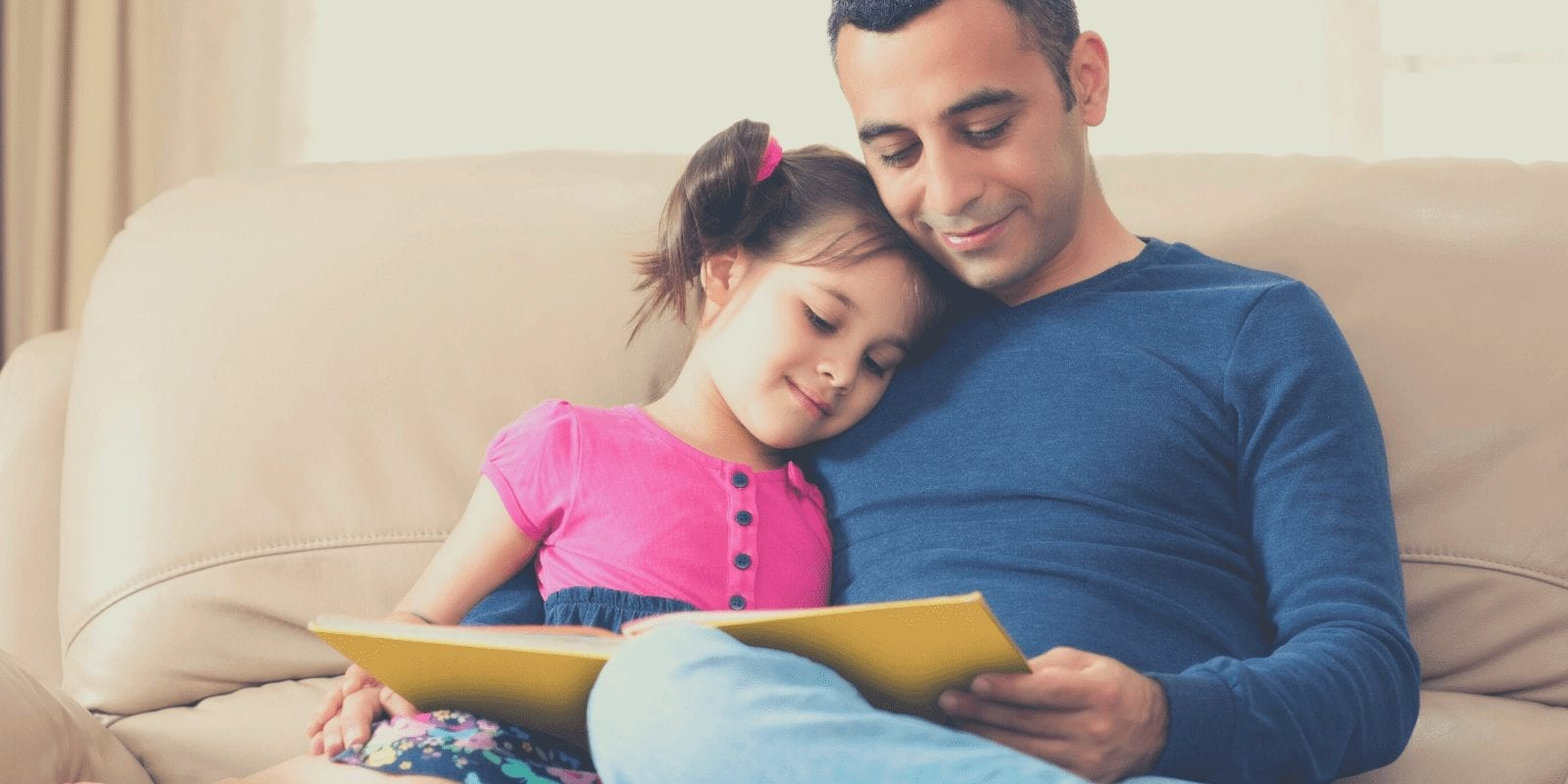 A dad and a daughter are sitting on the couch reading