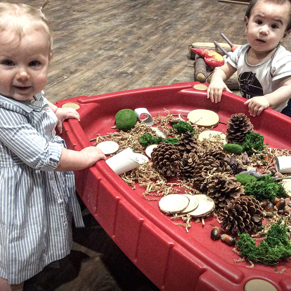Two kids playing with pine cones at Little Sunshine's Playhouse and Preschool
